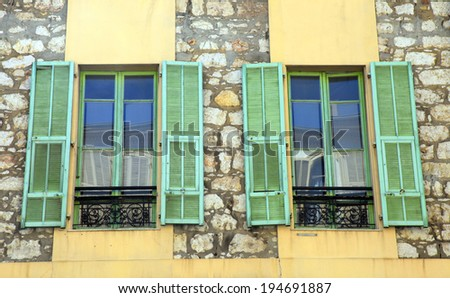 Two french rustic windows with old green shutters in stone rural house, Provence, France. - stock photo