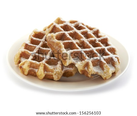 two fresh and tasty belgian sugar waffles served on a plate, sprinkled with nice sweet powder sugar - stock photo