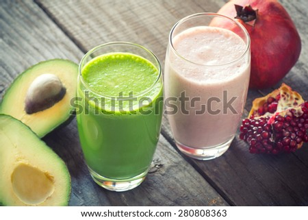 two fresh blended fruit smoothies made with avocado, pomegranate - stock photo