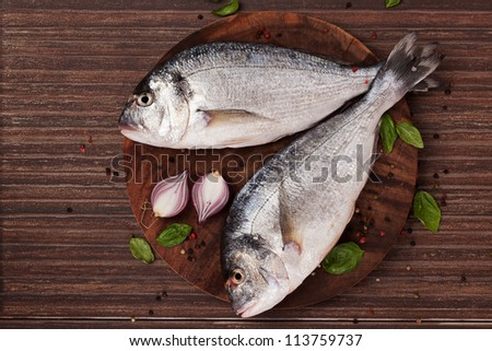 Two fresh gilt hear sea bream on round wooden chopping board with fresh basil leaves, colorful peppercorn and onion, top view. Seafood coocking ingredients in natural brown. - stock photo