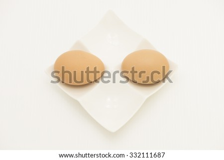Two fresh hard boiled eggs on opposite side of each other on white ceramic egg plate.  Isolated on white background. - stock photo