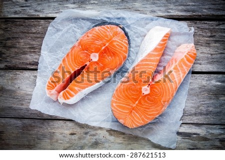Two fresh raw salmon steak on a paper on the rustic table - stock photo