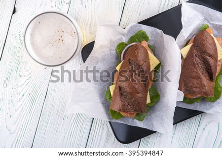 Two fresh sandwiches with fish and vegetables and beer glass - stock photo