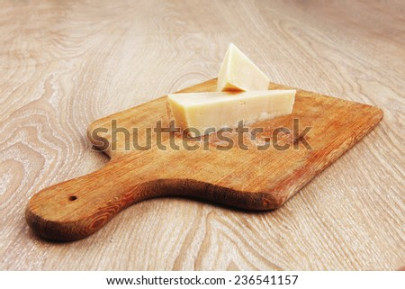 two fresh triangle french delicacy parmesan cheese pieces on wooden cut board over table - stock photo