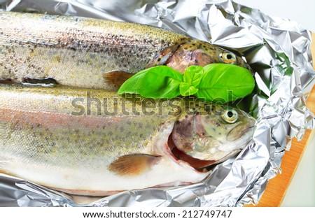 Two fresh trout on tin foil - stock photo