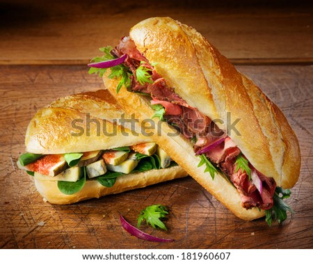 Two freshly baked crisp crusty baguettes filled with figs, spinach and blue cheese and gourmet cold roast beef for a delicious takeaway or savory lunch - stock photo