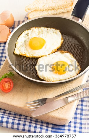 Two fried eggs in a frying pan - stock photo