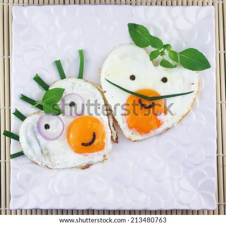 Two fried eggs shaped as hearts with faces. - stock photo