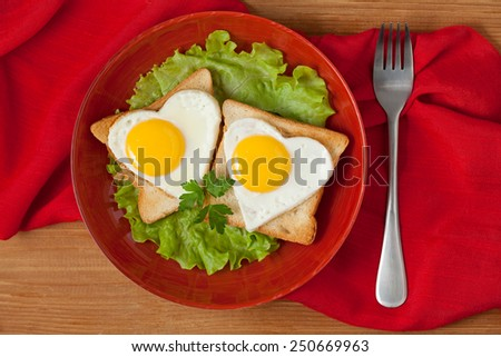 Two fried heart shaped eggs on toast with salad and coffee for Valentines Day or Easter on textile background - stock photo