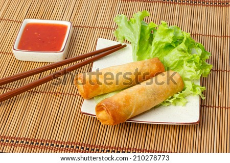 Two fried spring rolls on a plate served with chili sauce - stock photo