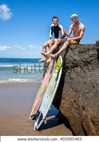 Two friend surfer sitting on rock showing sign OK. Two surfboards standing on the sand, leaning on a rocky big stone - stock photo