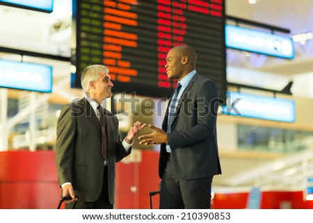 two friendly businessmen talking at airport - stock photo