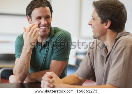 Two friendly male mature students chatting while sitting in class room - stock photo