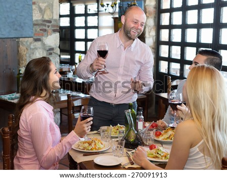 Two friendly married couple sitting at restaurant table - stock photo