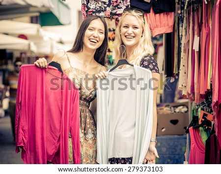 two friends at the shopping mall choosing clothes. concept about shopping, fashion, economy, women, clothing and people - stock photo