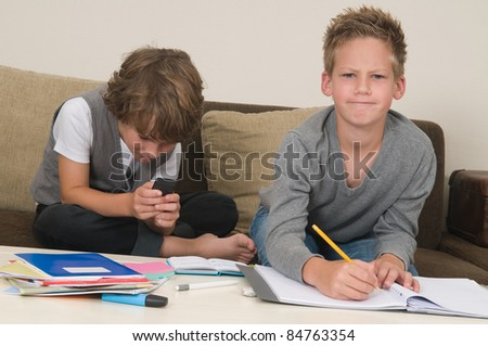 Two friends doing their homework in the livingroom. One of them is gaming, the other one is not ready and is jealous. - stock photo