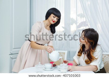 Two friends drink tea with cake. Tea party. Home gatherings. Woman pours tea girlfriend. - stock photo
