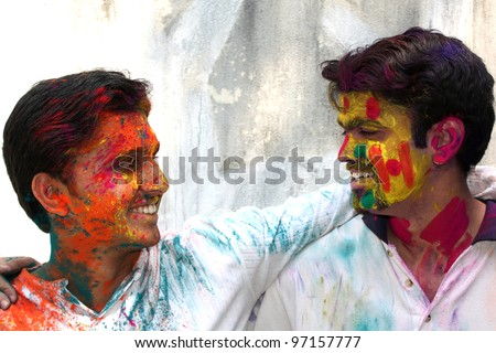 Two friends enjoying the colorful holi festival in India. - stock photo