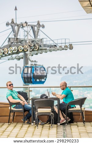 Two friends enjoying together outside at the cafe - stock photo