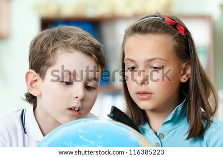 Two friends examine a school globe trying to find something - stock photo