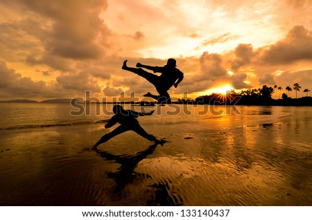 Two friends fighting when sunset moment near the beach - stock photo