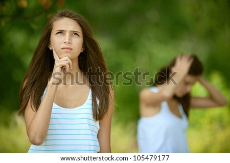 Two friends had falling out, against green of summer park. - stock photo