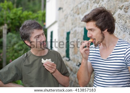 two friends having a snack and talking outdoors - stock photo
