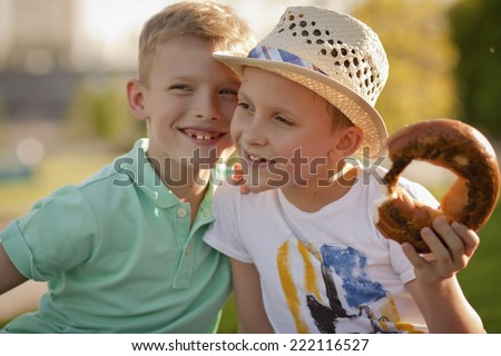 Two friends having fun talking in the park. One boy told a secret, the other is eating a muffin - stock photo