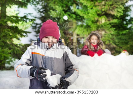 Two friends having snowball fight - stock photo