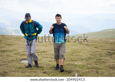 Two friends hiking together in mountains, with backpacks - stock photo