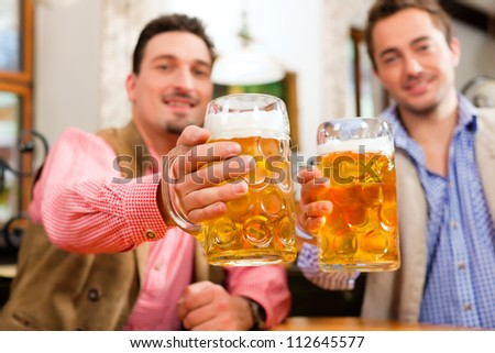 Two friends in Bavarian pub in traditional clothes sitting on their regular table in a pub - stock photo