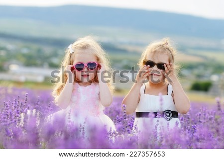 two friends in field wearing sunglasses - stock photo