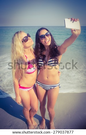 two friends in swimsuits taking a selfie at the beach - stock photo