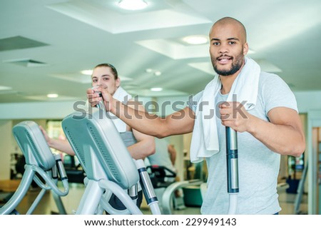 Two friends in the train. Workout in the gym in the cardio room. Two athletes engaged in the simulator gym - stock photo
