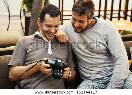 Two friends looking at photos in camera - stock photo