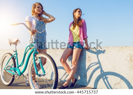Two friends out for a bike ride at the seaside - stock photo