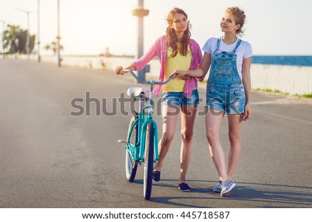 Two friends out for a bike ride at the seaside. Stylish casual outfit. Evening sunset, students, happy time, toned colors. - stock photo