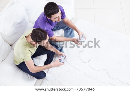 Two friends play video games - stock photo