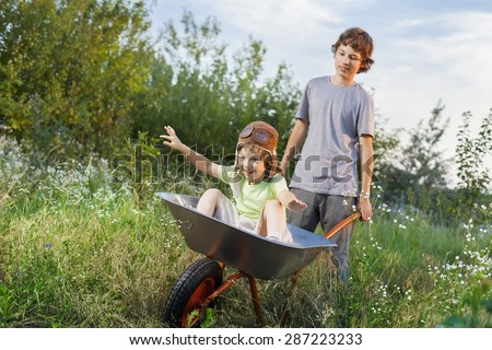 two friends playing in the plane using a garden carts - stock photo