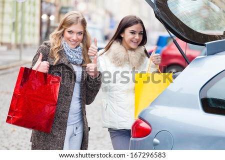 Two friends putting a shopping bags in the car  - stock photo