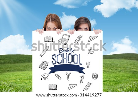 Two friends secretly hiding behind a blank poster against blue sky over green field - stock photo