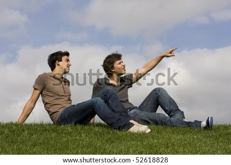 Two friends sit on the grass looking up - stock photo