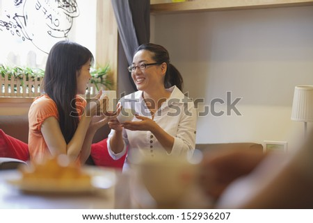 Two friends sitting in a coffee shop and talking - stock photo
