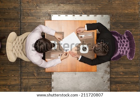 two friends sitting in cafe and eating lunch. top view of two colleagues met in restaurant - stock photo