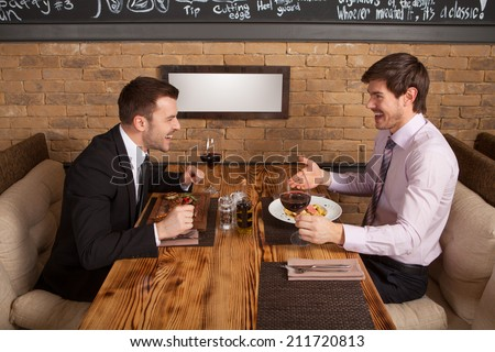 two friends sitting in cafe and eating lunch. two colleagues met in restaurant to discuss business - stock photo