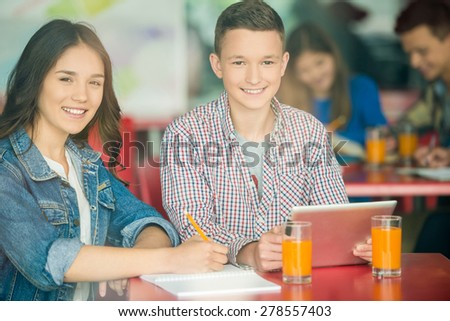 Two friends sitting in school cafe, studying and drinking orange juice. - stock photo