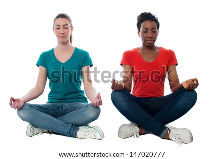 Two friends sitting together and meditating - stock photo