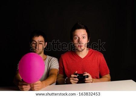 Two friends  sitting together, one gaming the other bored, a  concept - stock photo
