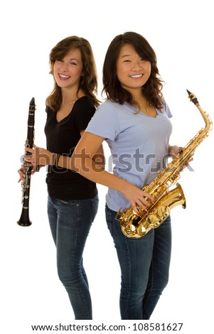Two friends stand back to back with woodwind instruments - stock photo