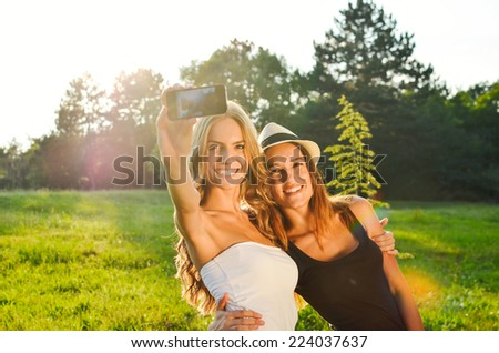 Two friends taking a selfie in a park - stock photo
